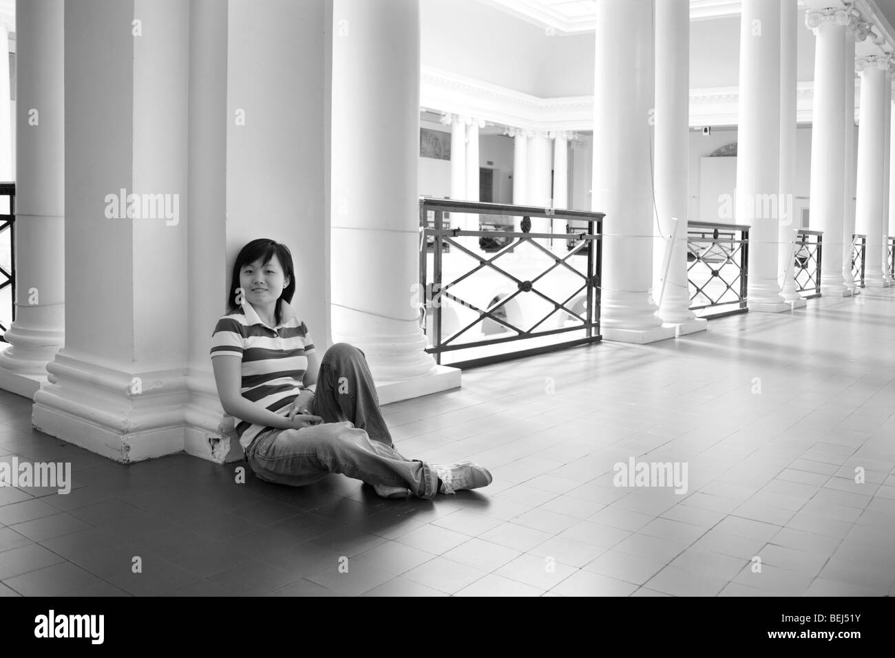 Young Chinese girl sitting in a very grand upper balcony with columns. - Stock Image