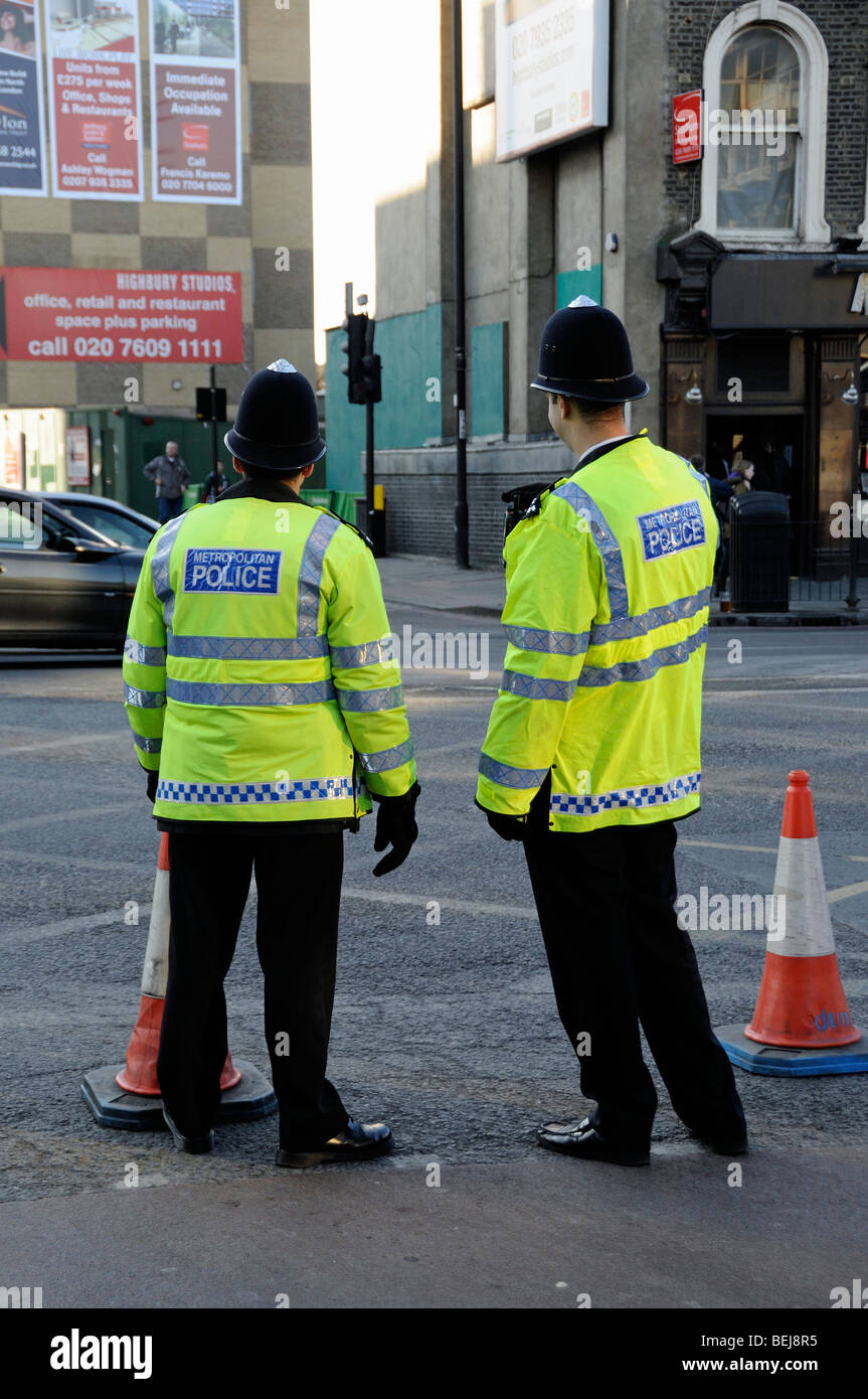 Two Metropolitan Police Officers from behind with traffic cones in Holloway Road London England UK - Stock Image