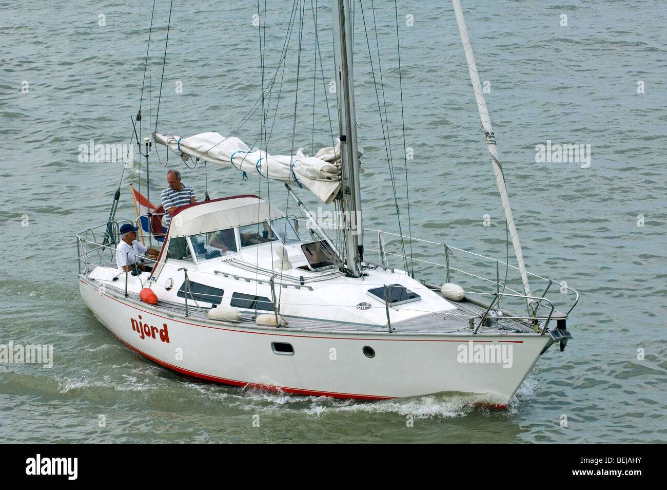 Sailing boat entering port with lowered sails, Belgium - Stock Image