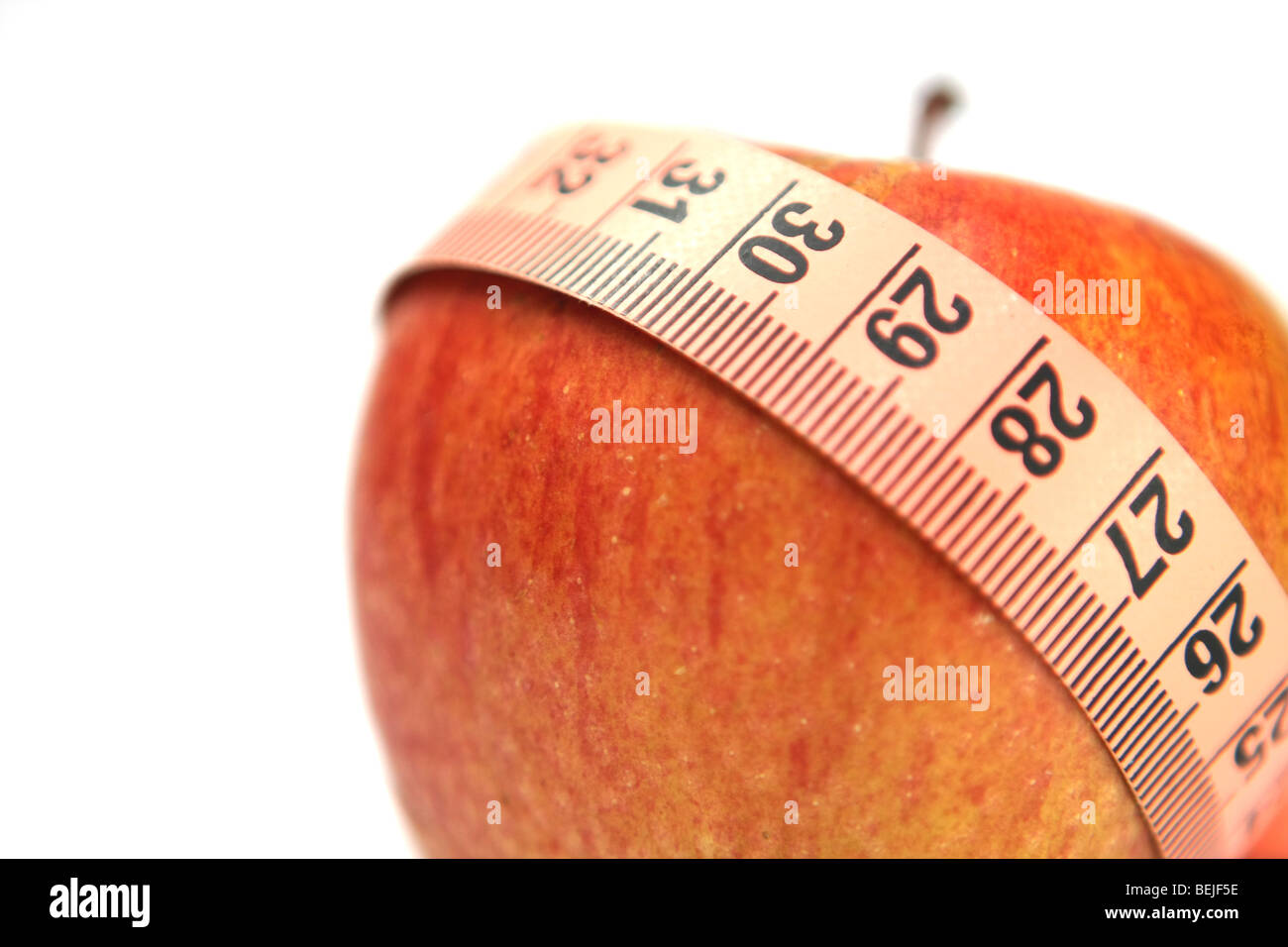 Diet concep Cutout of a tape measure wrapped around an apple on white background - Stock Image