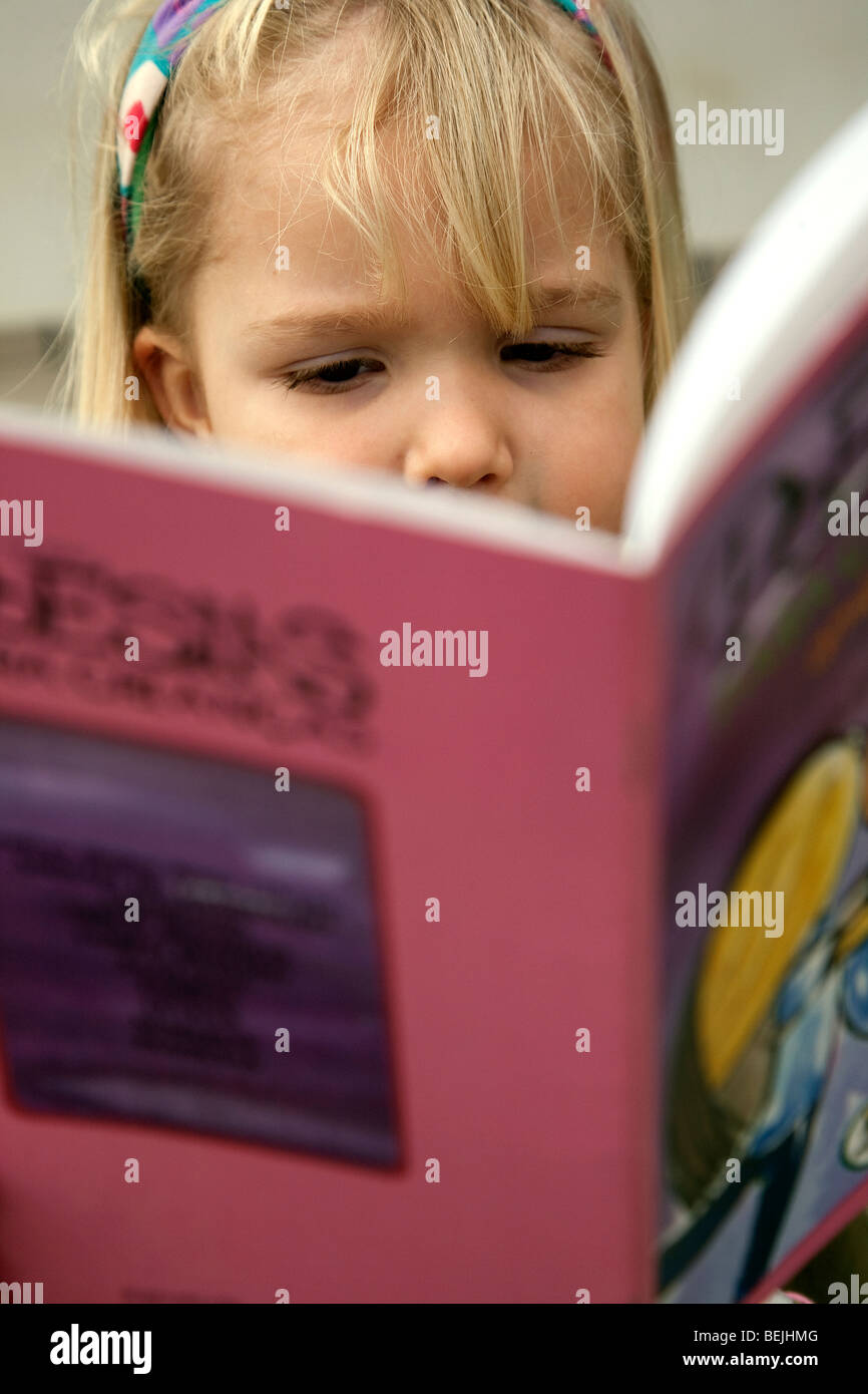 Nina with reading a book to her doll at home. - Stock Image