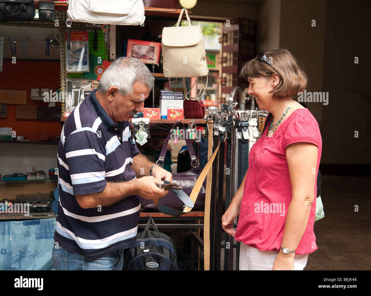 A tourist buying a leather belt in the market, Funchal, Madeira - Stock Image