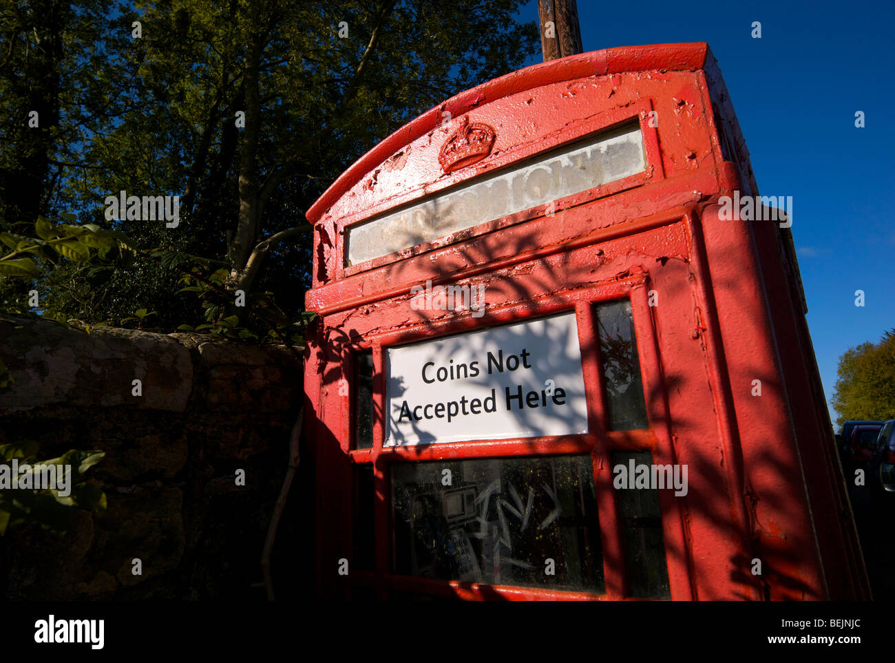 An old style telephone kiosk that no longer accepts coins as payment - Stock Image