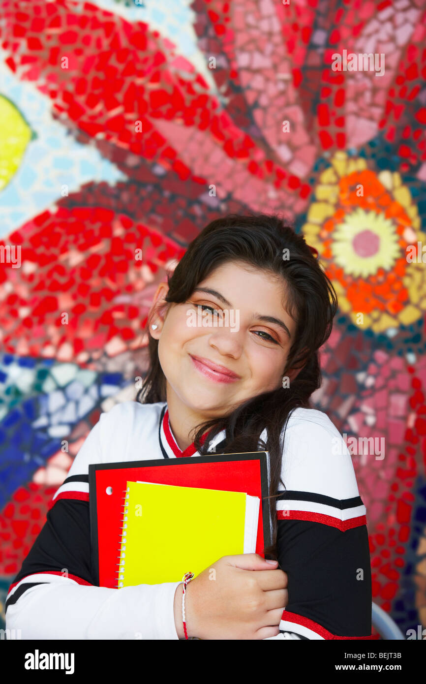 Portrait of a cheerleader holding books and smirking - Stock Image