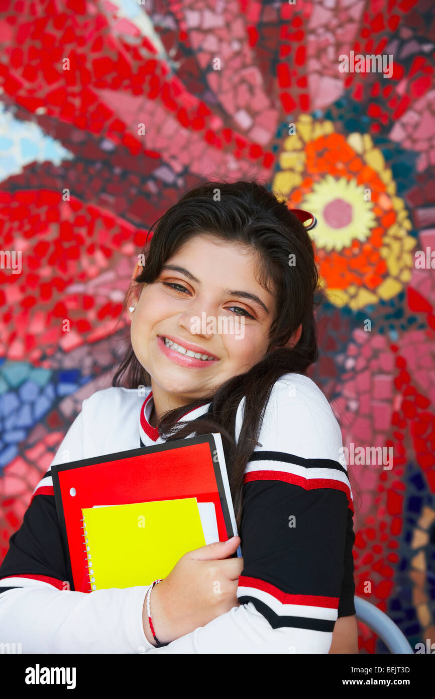 Portrait of a cheerleader holding books and smiling - Stock Image