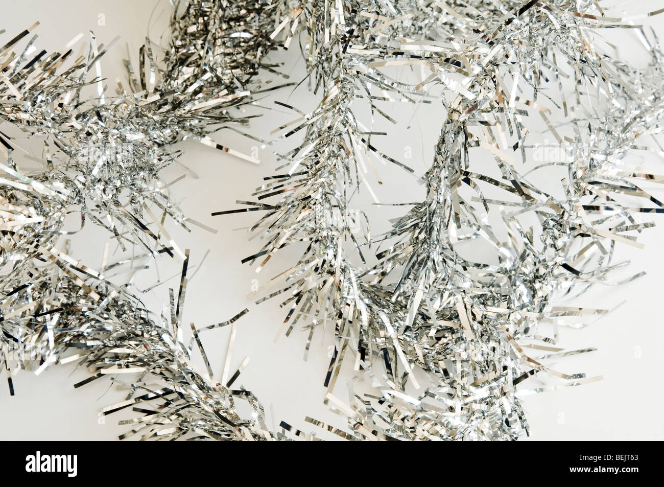 Silver Christmas Tinsel on a white background - Stock Image