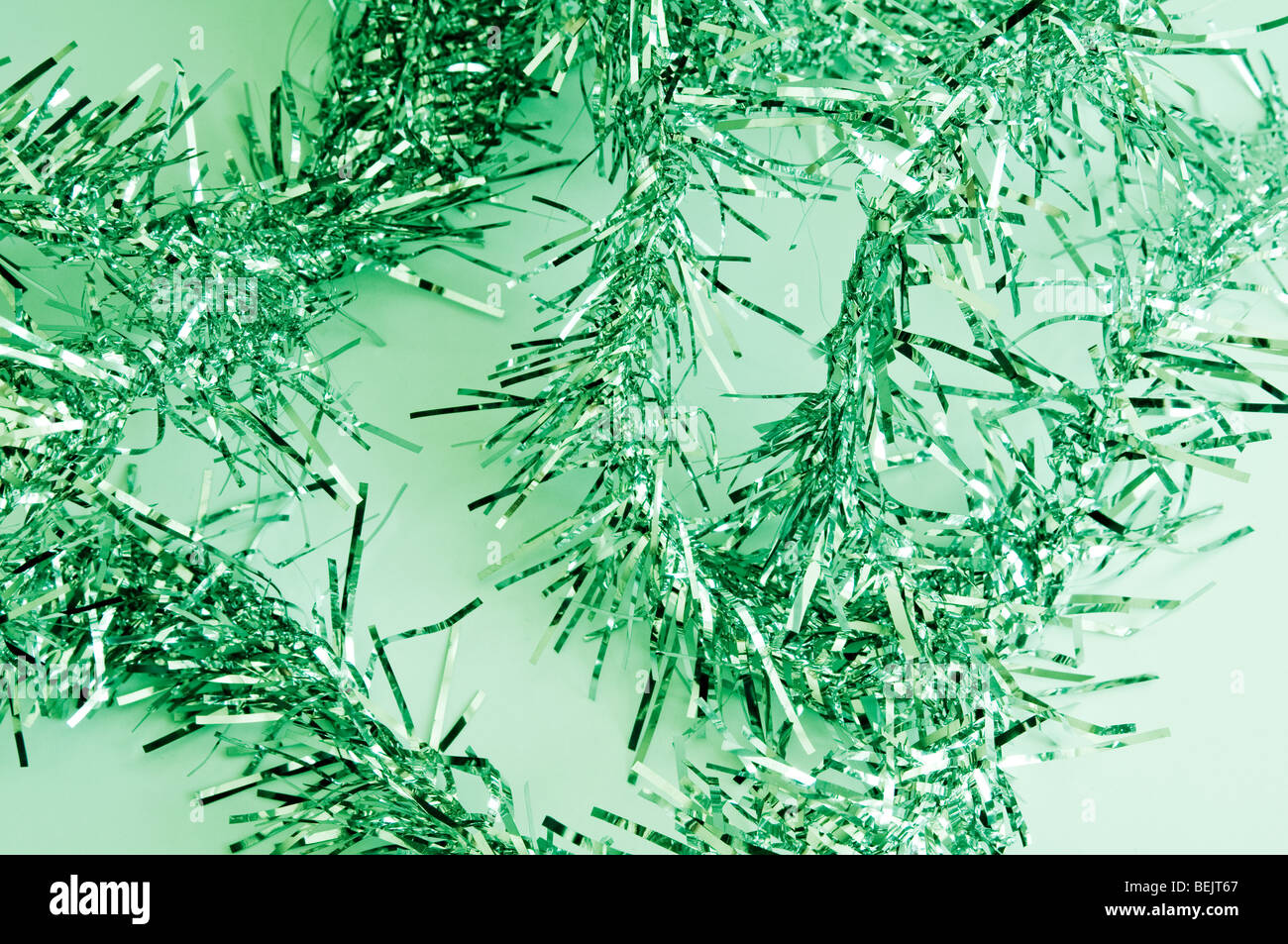 Green Christmas Tinsel on a pale green background - Stock Image