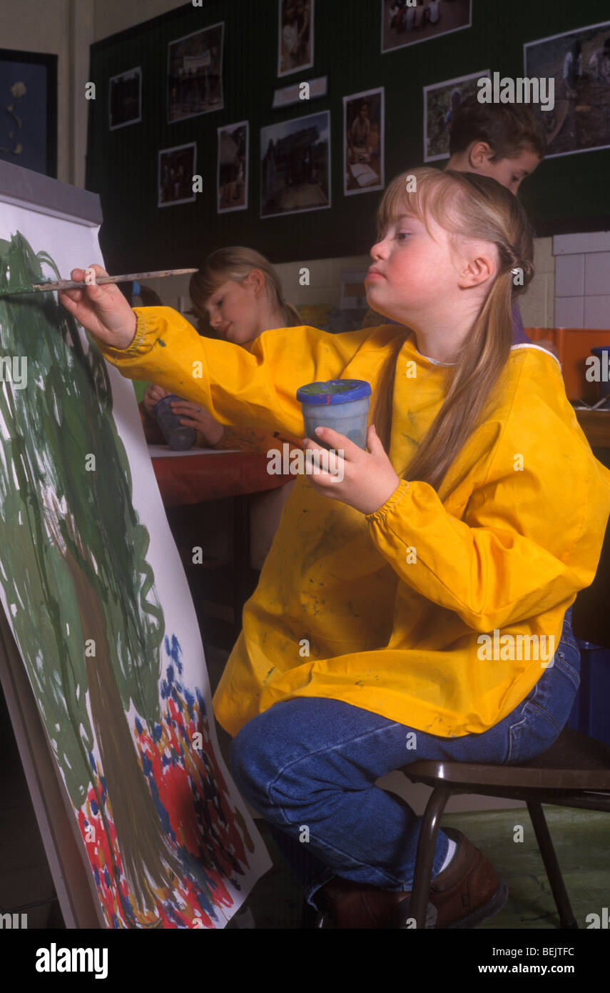 little girl with down's syndrome at mainstream school in an art class - Stock Image