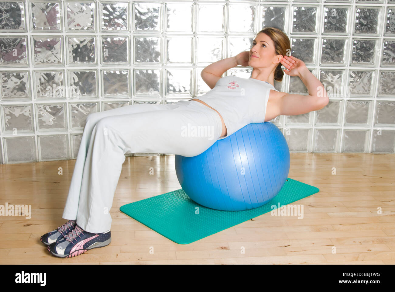Woman using exercise ball to train / work out in a gymnasium - Stock Image