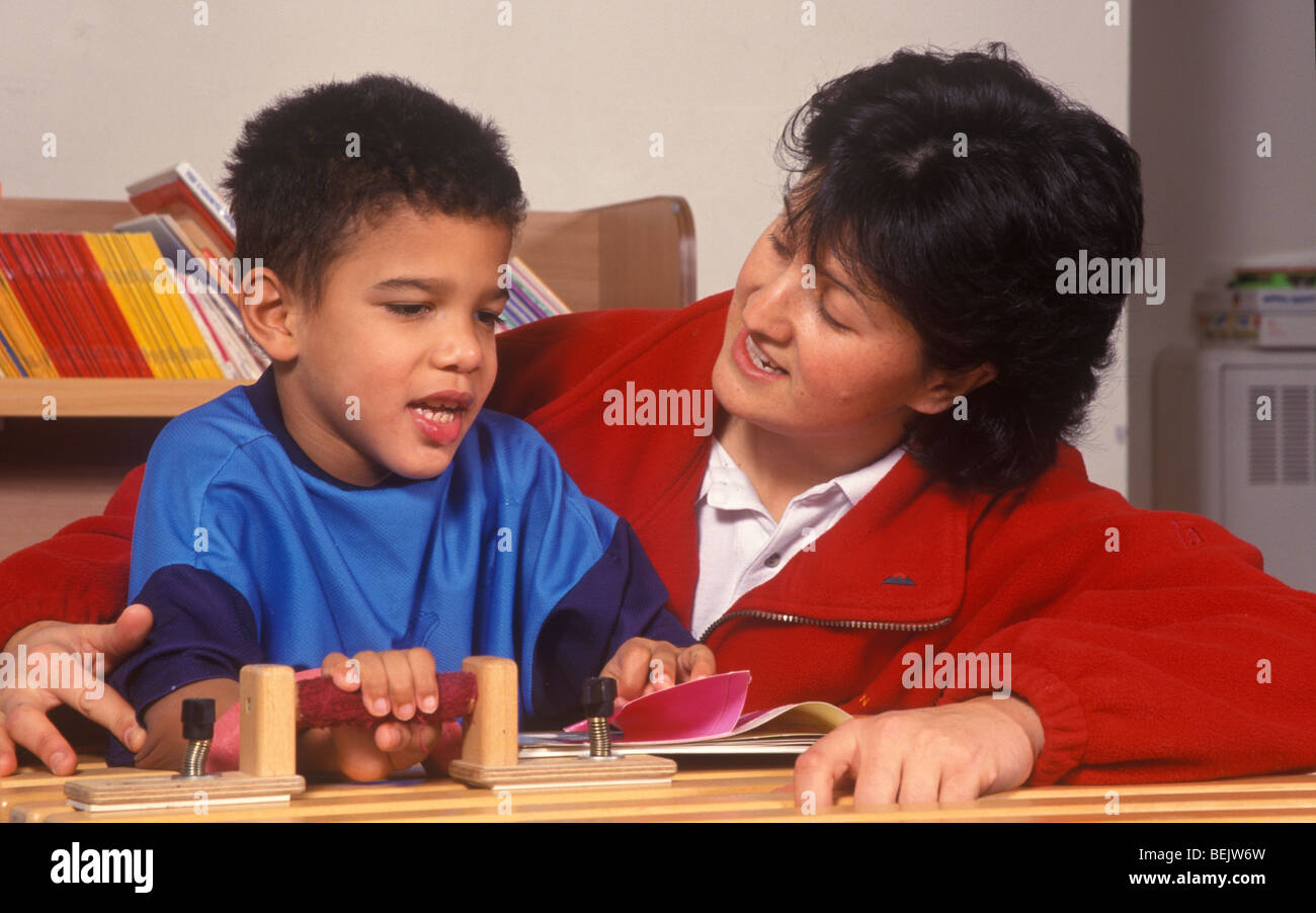mixed race little boy with cerebral palsy in the classroom with his teacher - Stock Image