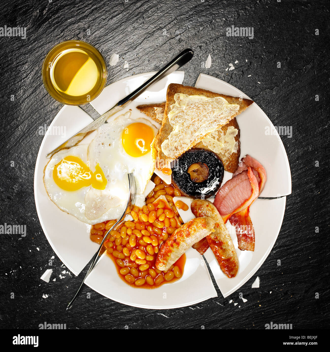 A full breakfast containing bacon, eggs, sausage, baked beans, mushroom and toast Stock Photo