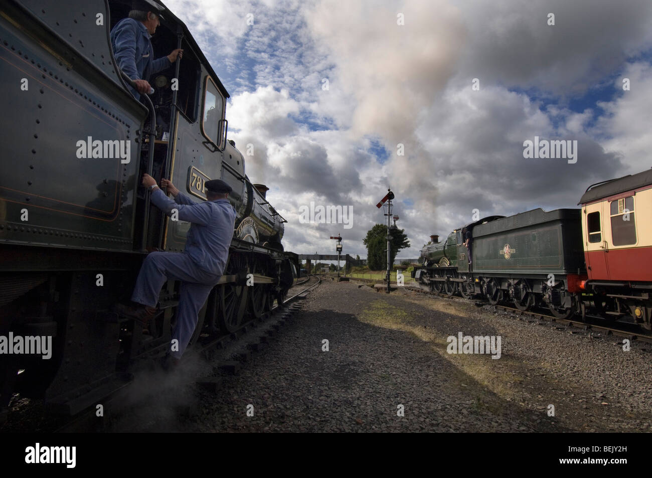 An engine driver climbing into the cab of a steam train on the preserved  Severn Valley Railway at Kidderminster, - Stock Image