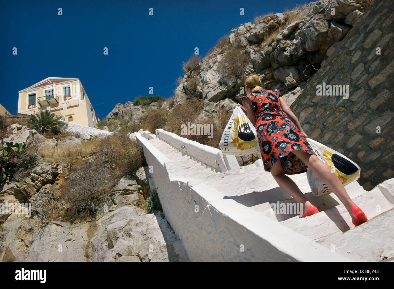 A woman with two bags of heavy shopping climbs steep steps to a house on the Greek island of Symi Stock Photo