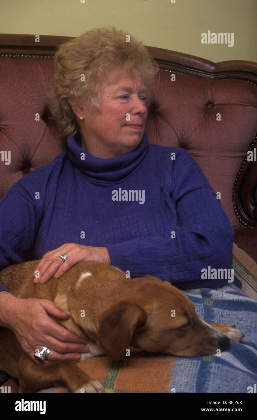 elderly woman cuddling a dog that resembles her - Stock Image