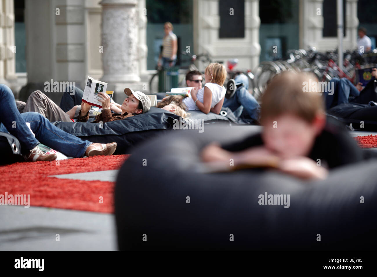 People read while lying on beanbag cushions at an outdoor library in the Hauptplatz in the city of Graz in Austria - Stock Image
