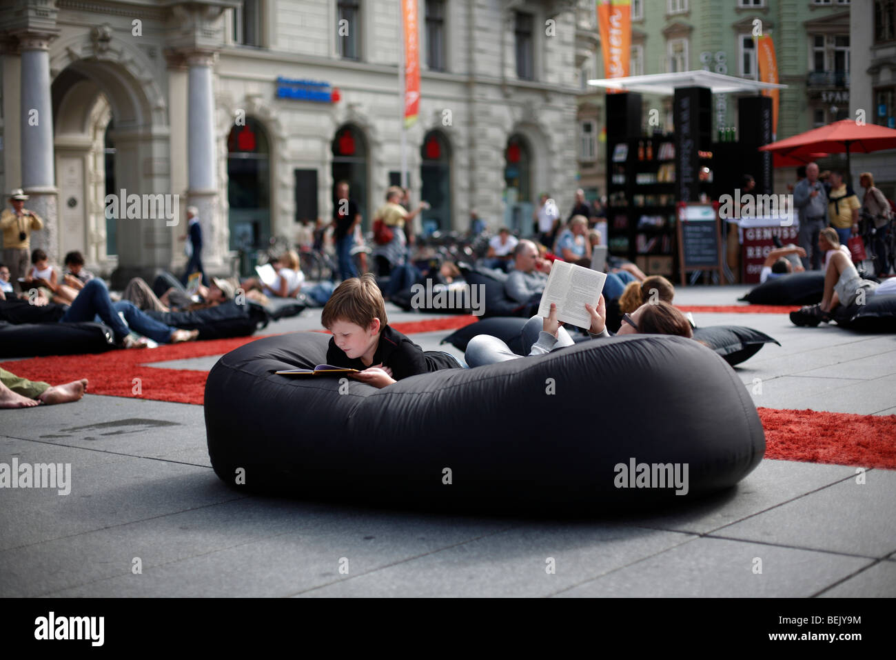 A boy reads on a beanbag cushion at an outdoor library in the Hauptplatz in the city of Graz in Austria - Stock Image