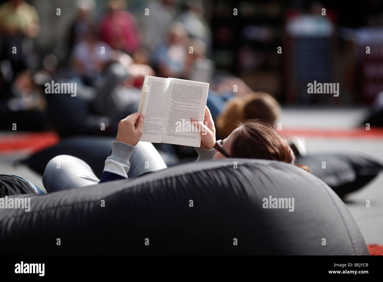 A girl reads on a beanbag cushion at an outdoor library in the Hauptplatz in the city of Graz in Austria - Stock Image