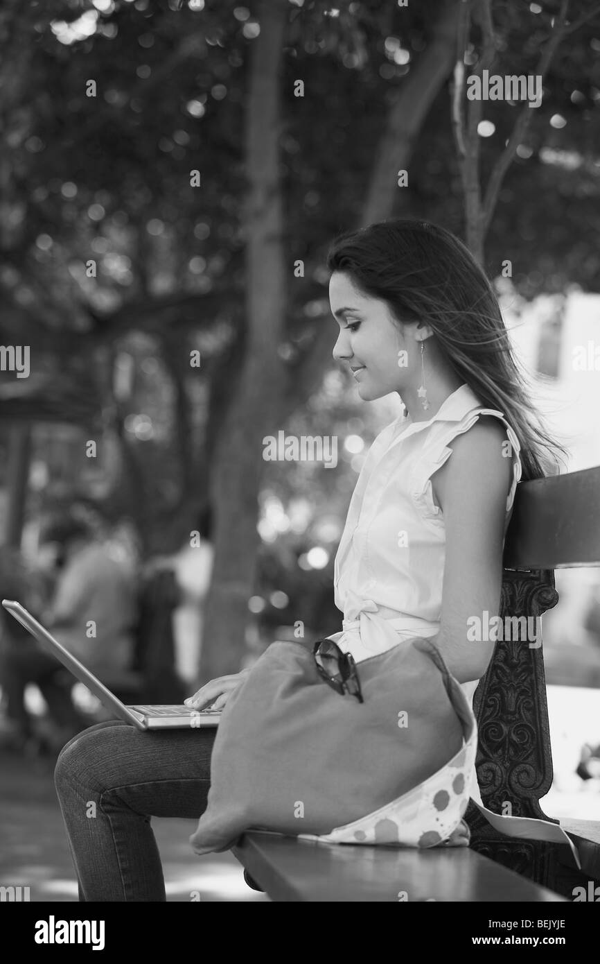 Side profile of a young woman sitting on a bench and using a laptop, Old San Juan, San Juan, Puerto Rico - Stock Image