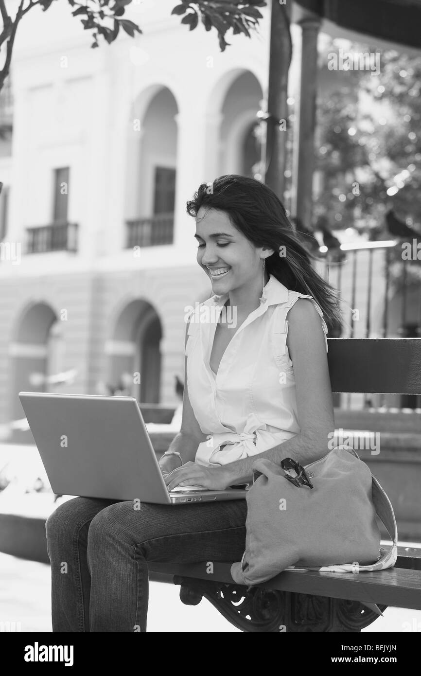 Close-up of a young woman sitting on a bench and using a laptop, Old San Juan, San Juan, Puerto Rico - Stock Image
