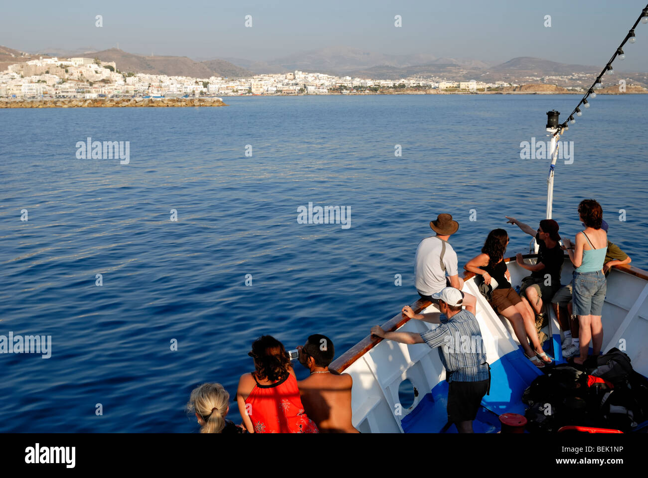 An excursion boat from Naousa, Paros Island, approach the harbour of Naxos town at the evening of a calm summer - Stock Image
