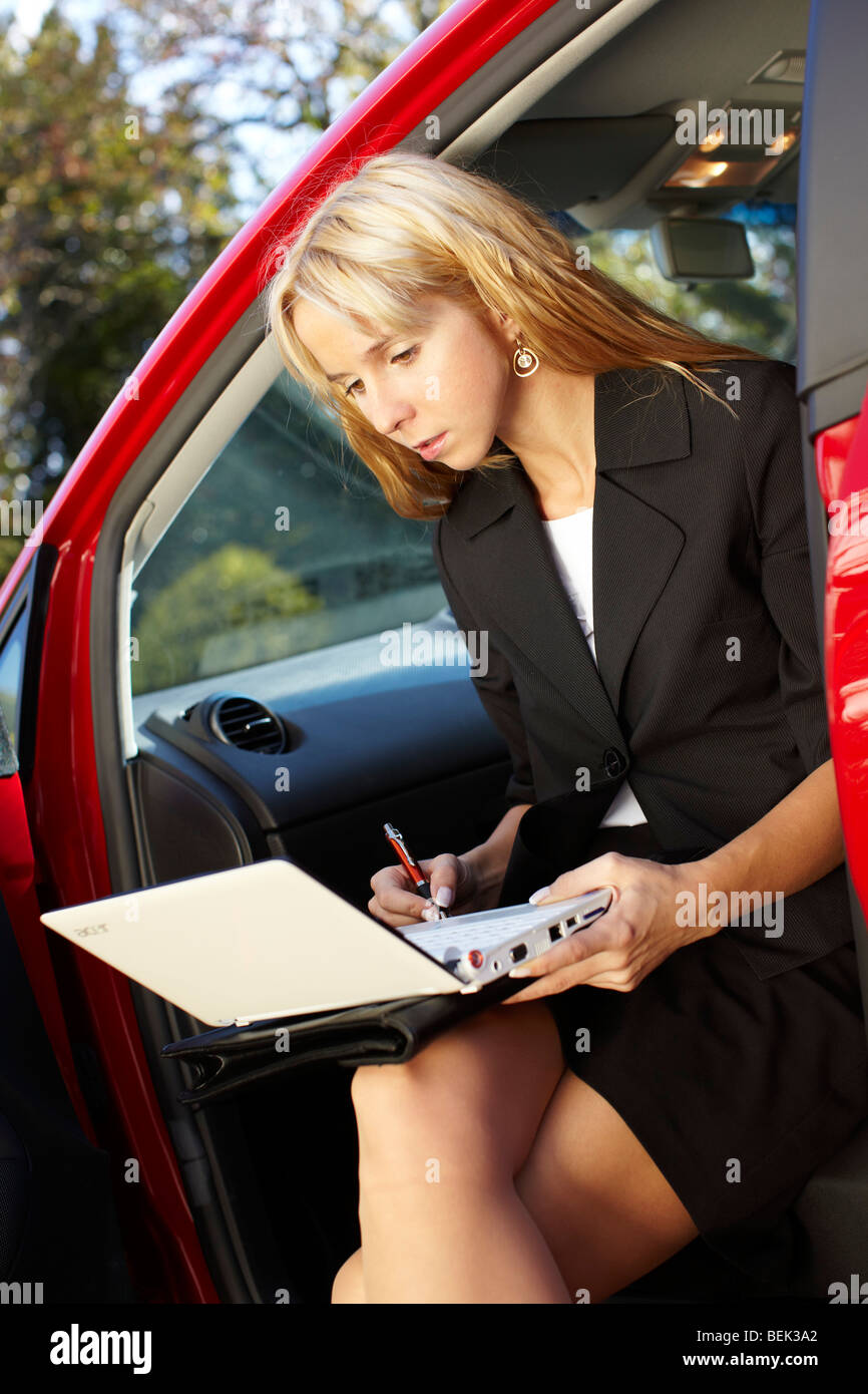 Woman sat in car with laptop - Stock Image