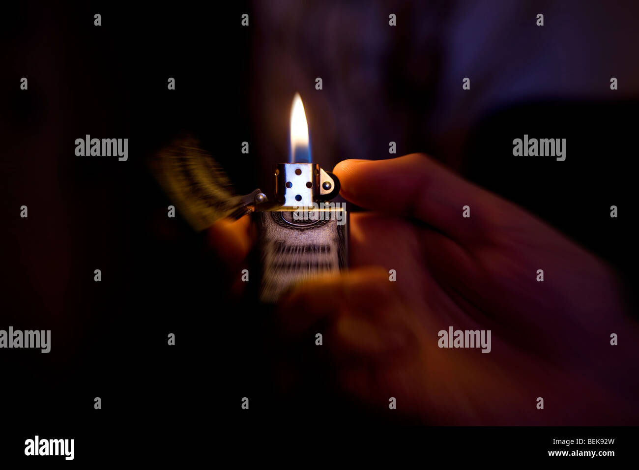 a man holding a zippo lighter in the dark - Stock Image