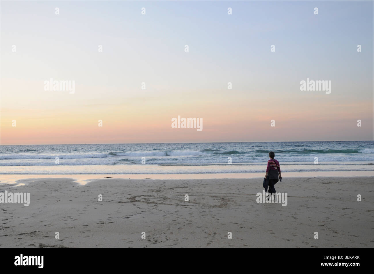A 40 year old woman walks on a Cornish beach at sunset - Stock Image