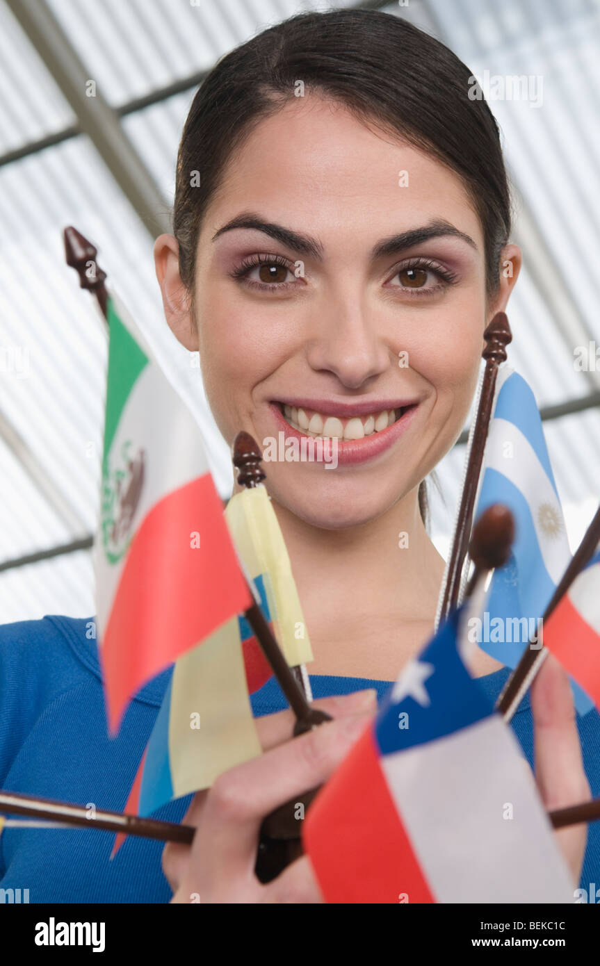 Portrait of a businesswoman holding flags and smiling - Stock Image
