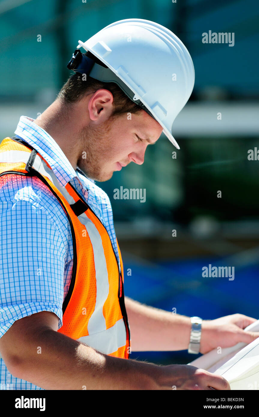 Civil Engineer Surveyor Checking Blueprintes Plans Wearing Safety Equipment On A New Construction Site Hi Vis Vest - Stock Image