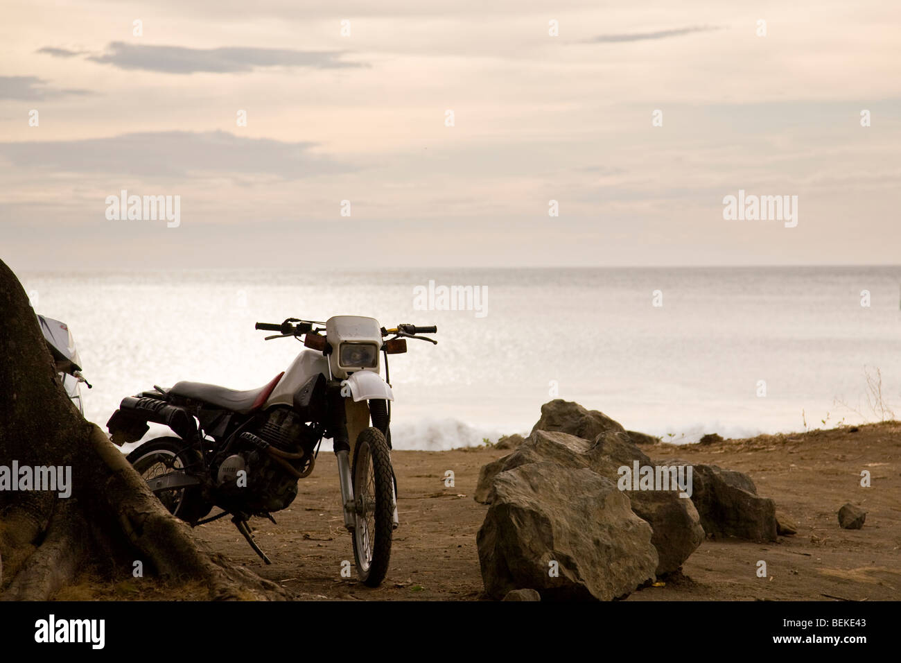 Dirt bike sitting on the beach in Playa del Coco, Guanacaste Province, Costa Rica. - Stock Image
