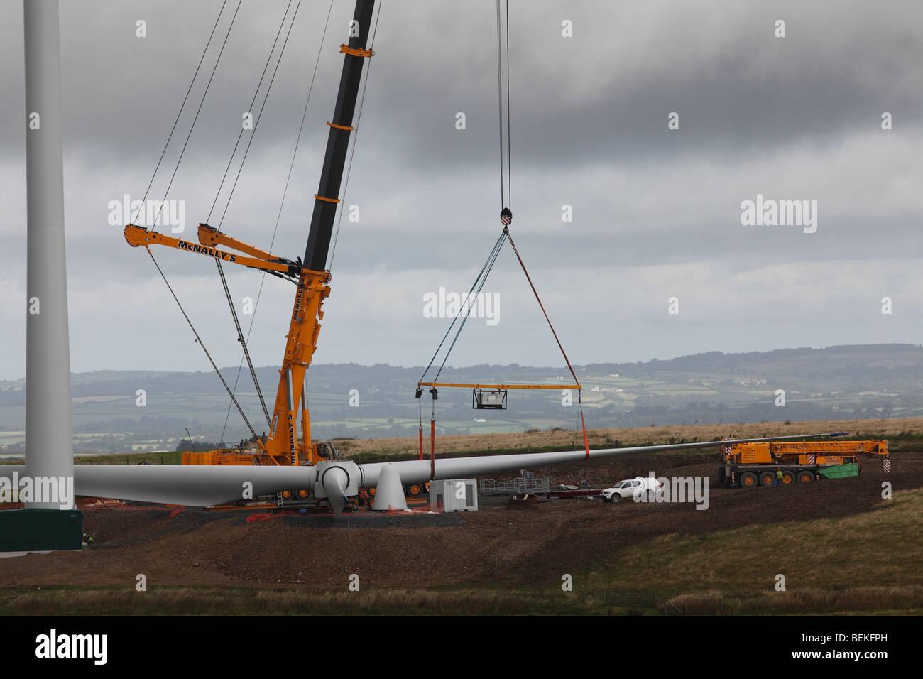 Assembling a wind turbine-fitting turbine blade to hub - Stock Image