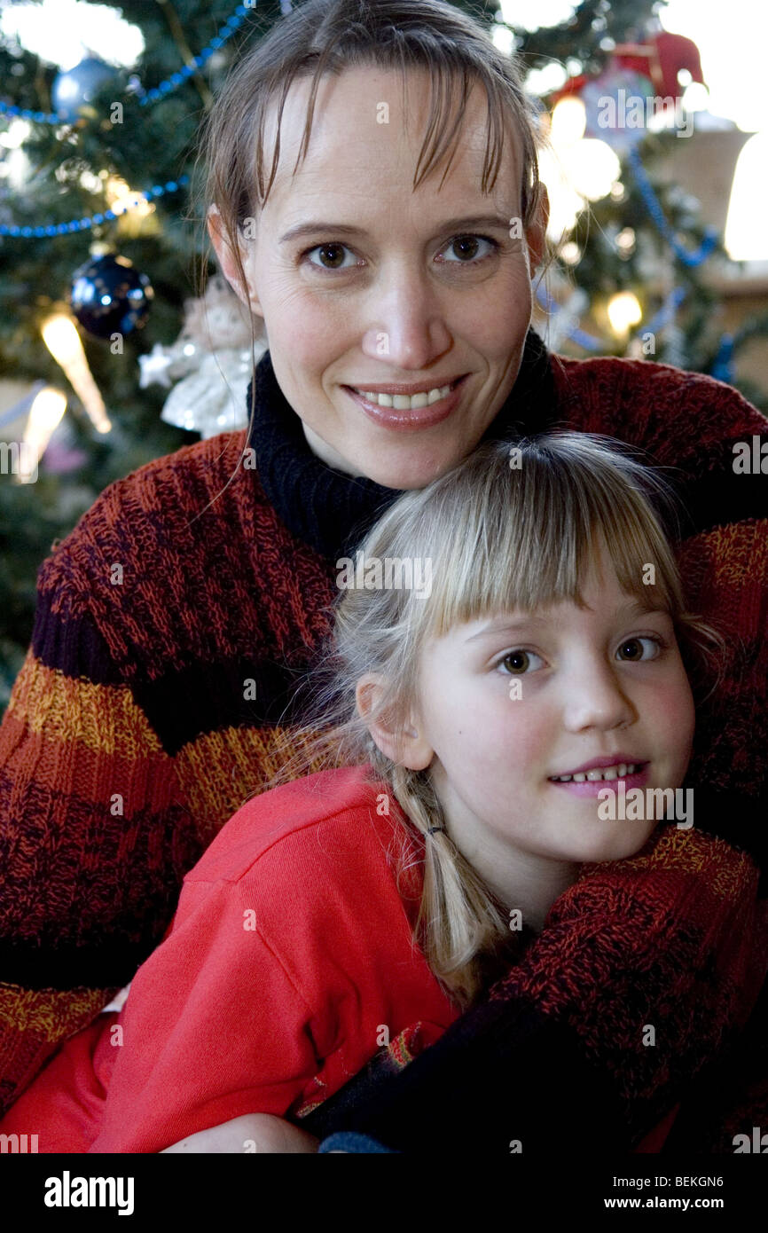 Happy mother and daughter posing looking at the camera in front of Christmas tree - Stock Image