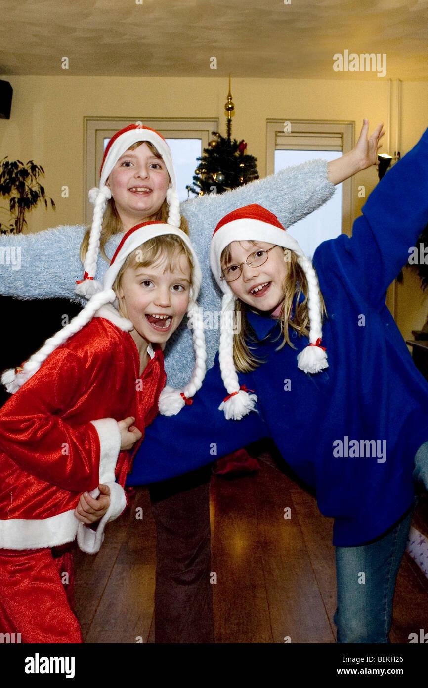 Cheery abundance children with santa hats posing - Stock Image