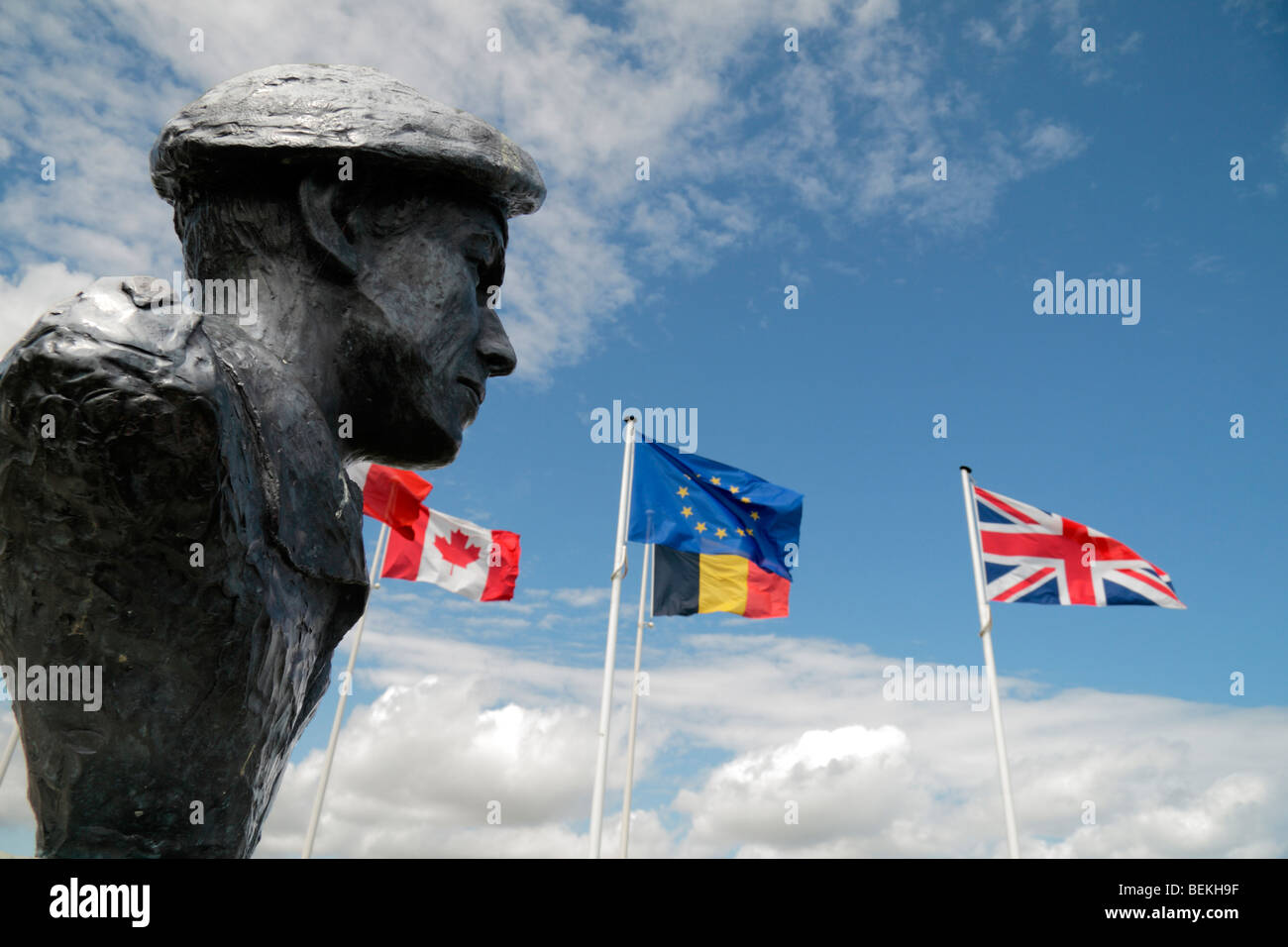 The EU and World War Two flags fly beside the bust to Lieutenant Colonel T Otway at the German Battery at Merville, Stock Photo