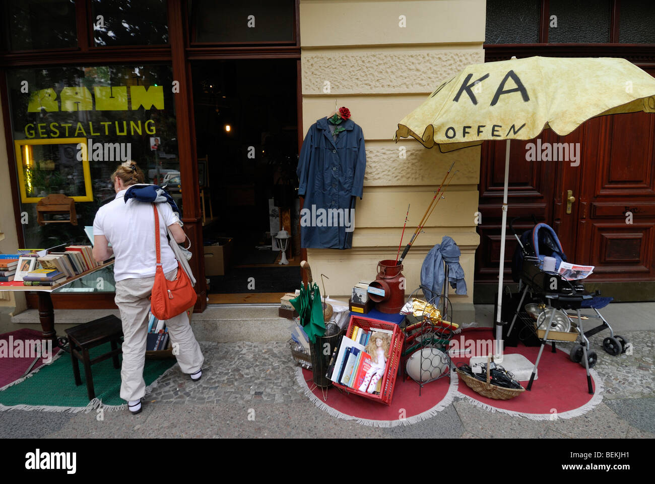 Berlin. Germany. Woman browsing a second hand shop in Prenzlauer Berg. - Stock Image