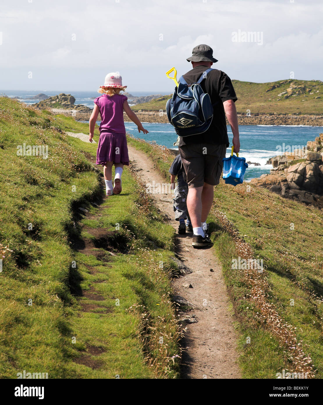 Father and children follow coastal path - Stock Image