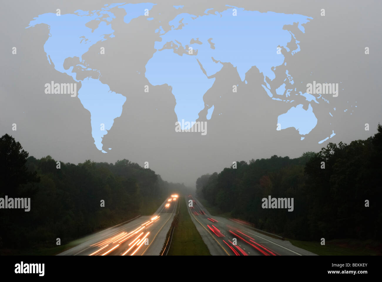 blue outline of a world map above a highway with cars on a grey, rainy evening - Stock Image