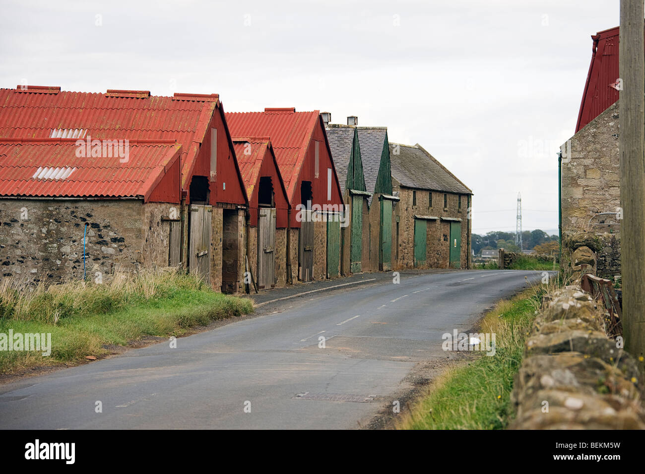 Farm buildings divided by public roads. - Stock Image