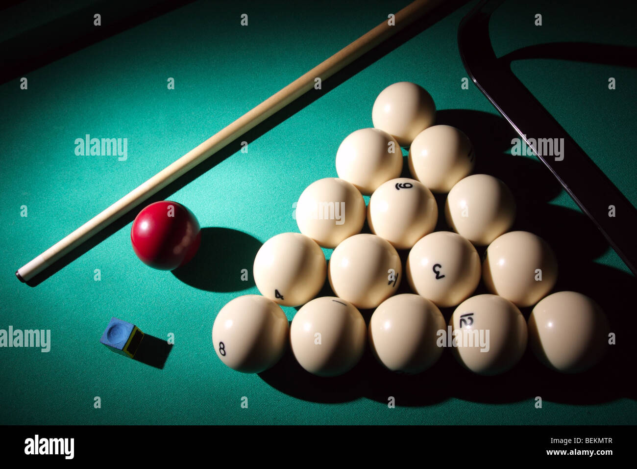 Pool balls on light beam. Balls pyramid with cue on a pool table. - Stock Image