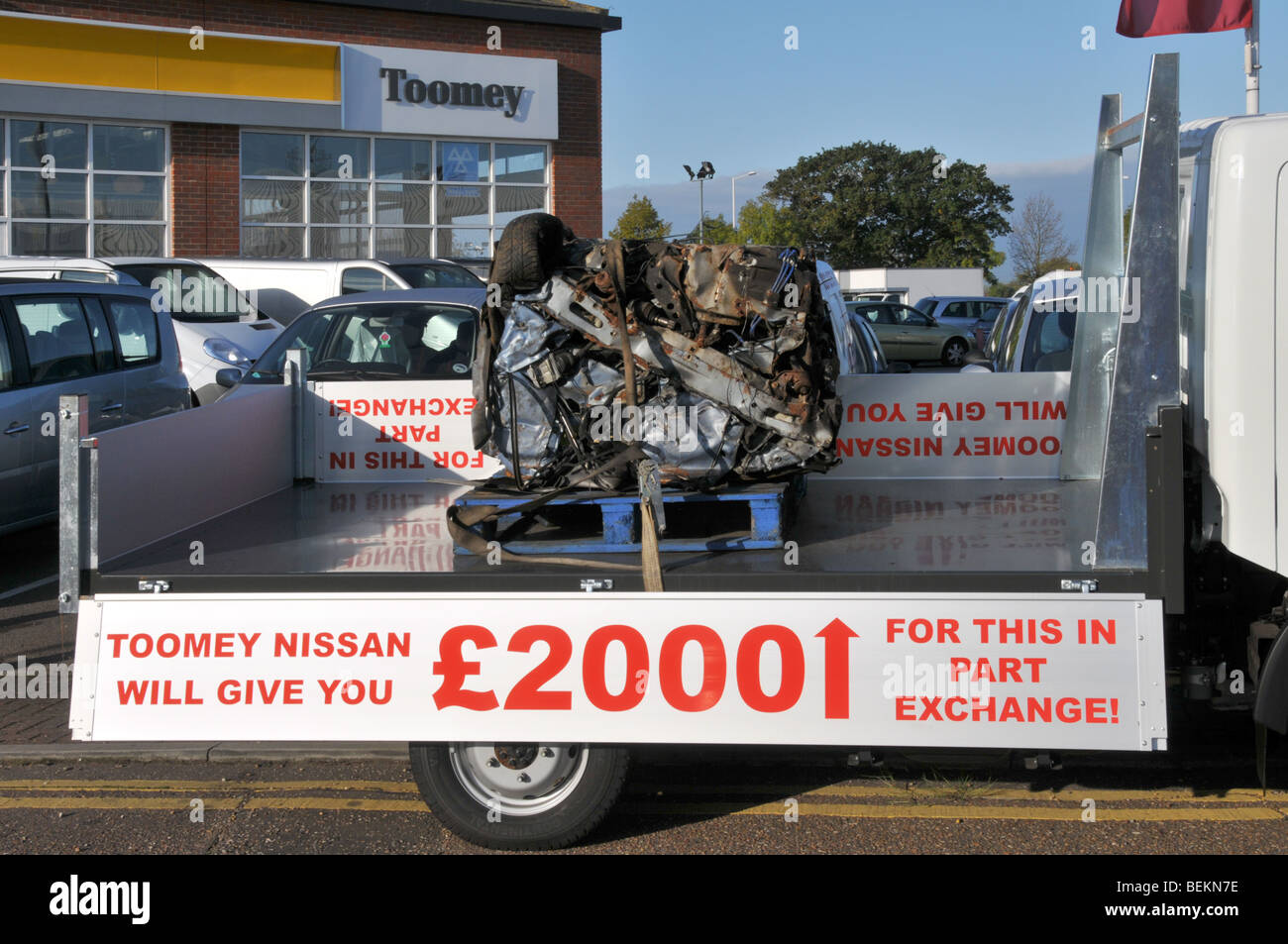 Nissan car dealer pickup truck carrying a crushed old car as Stock ...