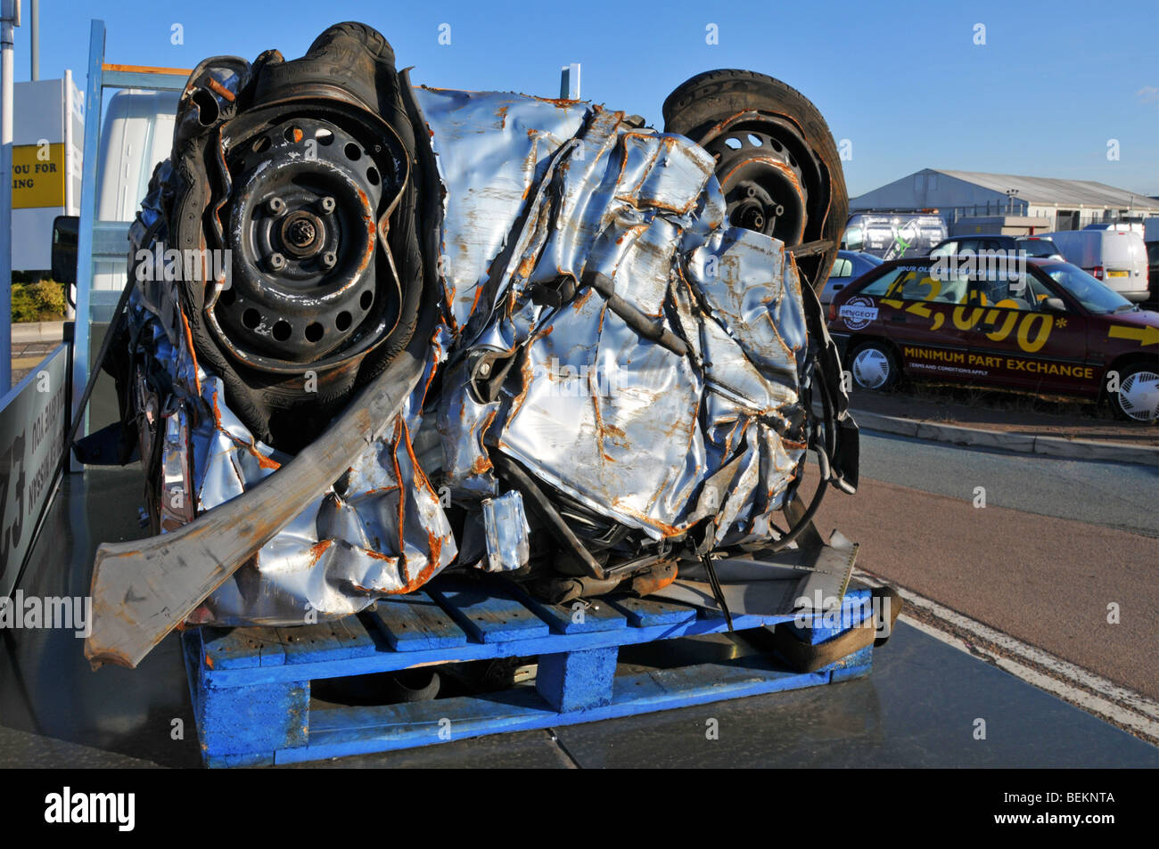 Scrapped motor car crushed into a cube for recycling in car dealers ...