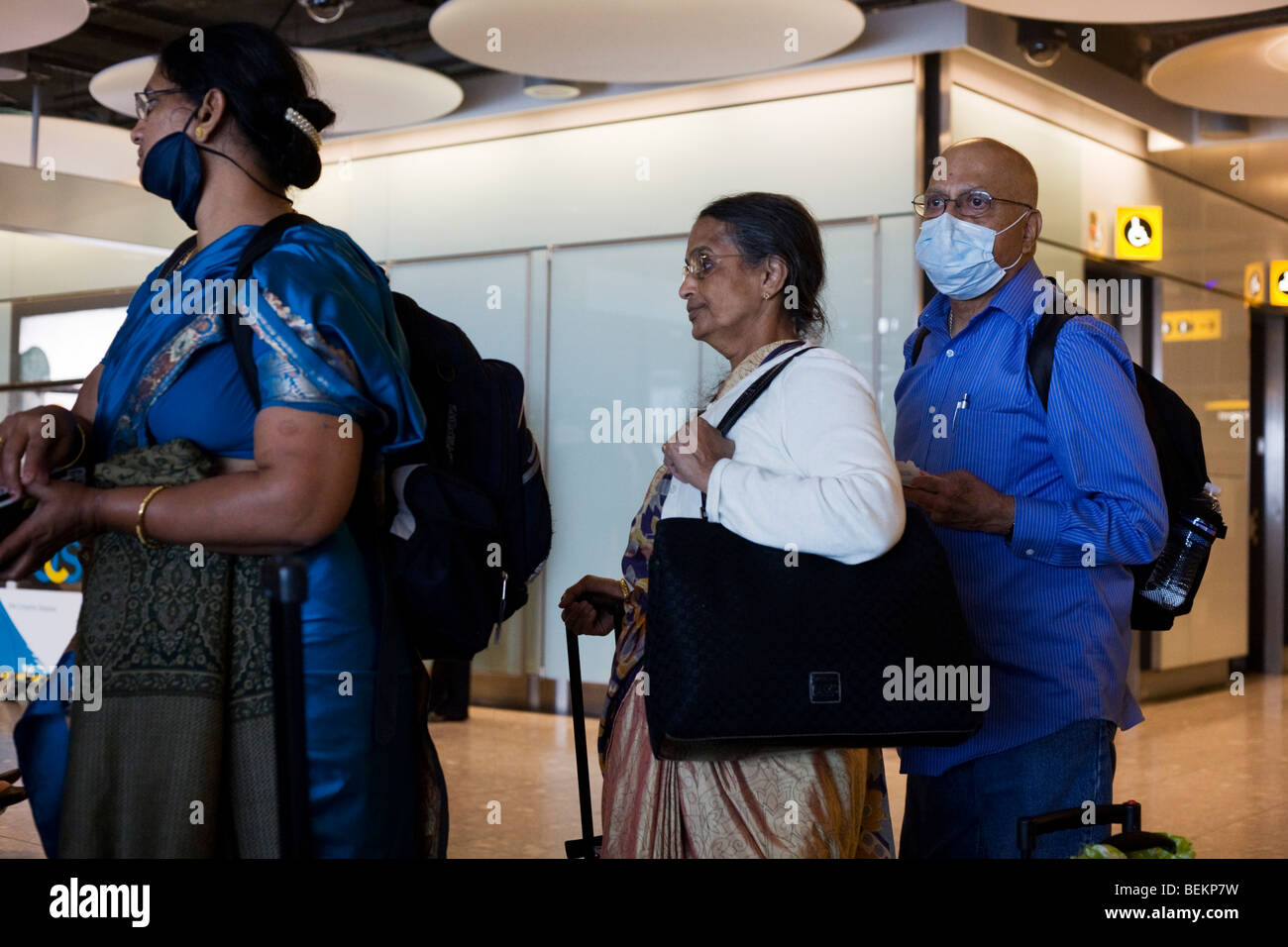 Airline passengers recently arrived from India wait in line at Heathrow Airport's Terminal 5 - Stock Image