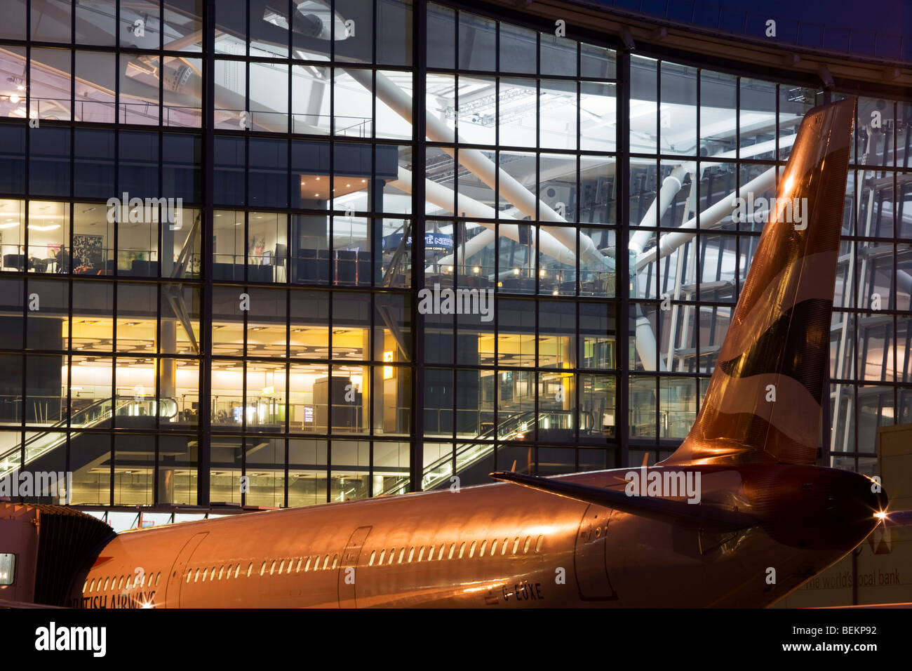 A British Airways jet aircraft is parked at night at a departure gate at Heathrow Airport's Terminal 5 building - Stock Image