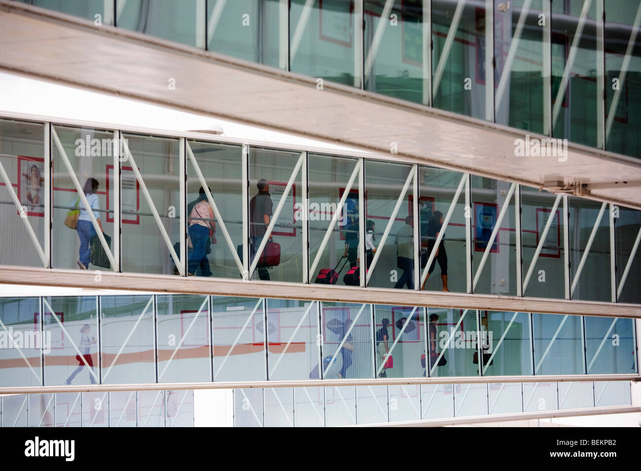 Airline passengers make their way along jetties from their newly-arrived aircraft, towards arrivals concourse, Heathrow - Stock Image
