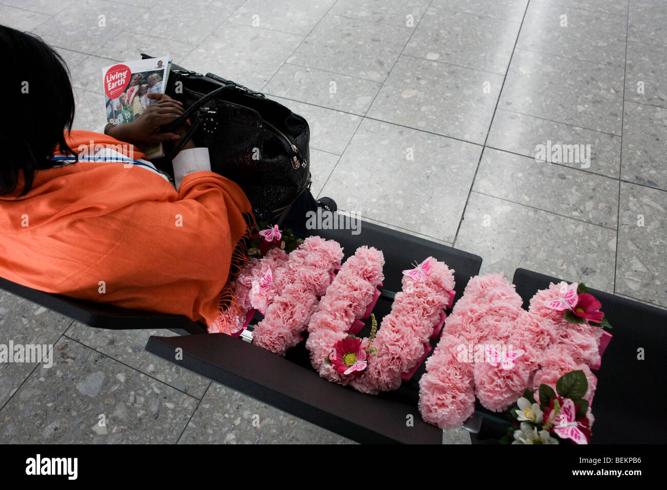 An airline passenger sits with a mother's funeral flowers in the departures concourse of Heathrow Airport's - Stock Image