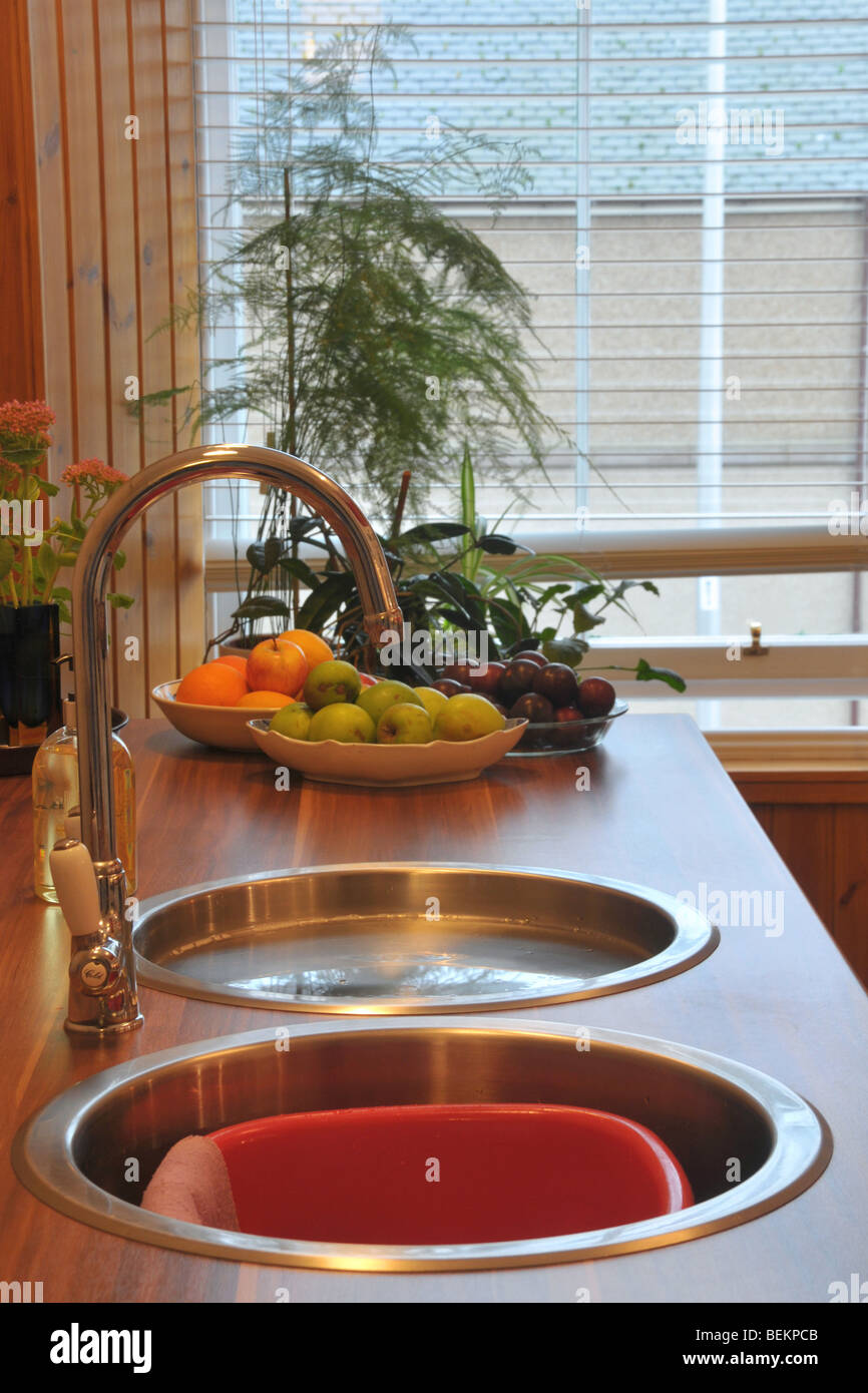 Two circular kitchen sinks and tap with fruit and potted plants in the background. - Stock Image