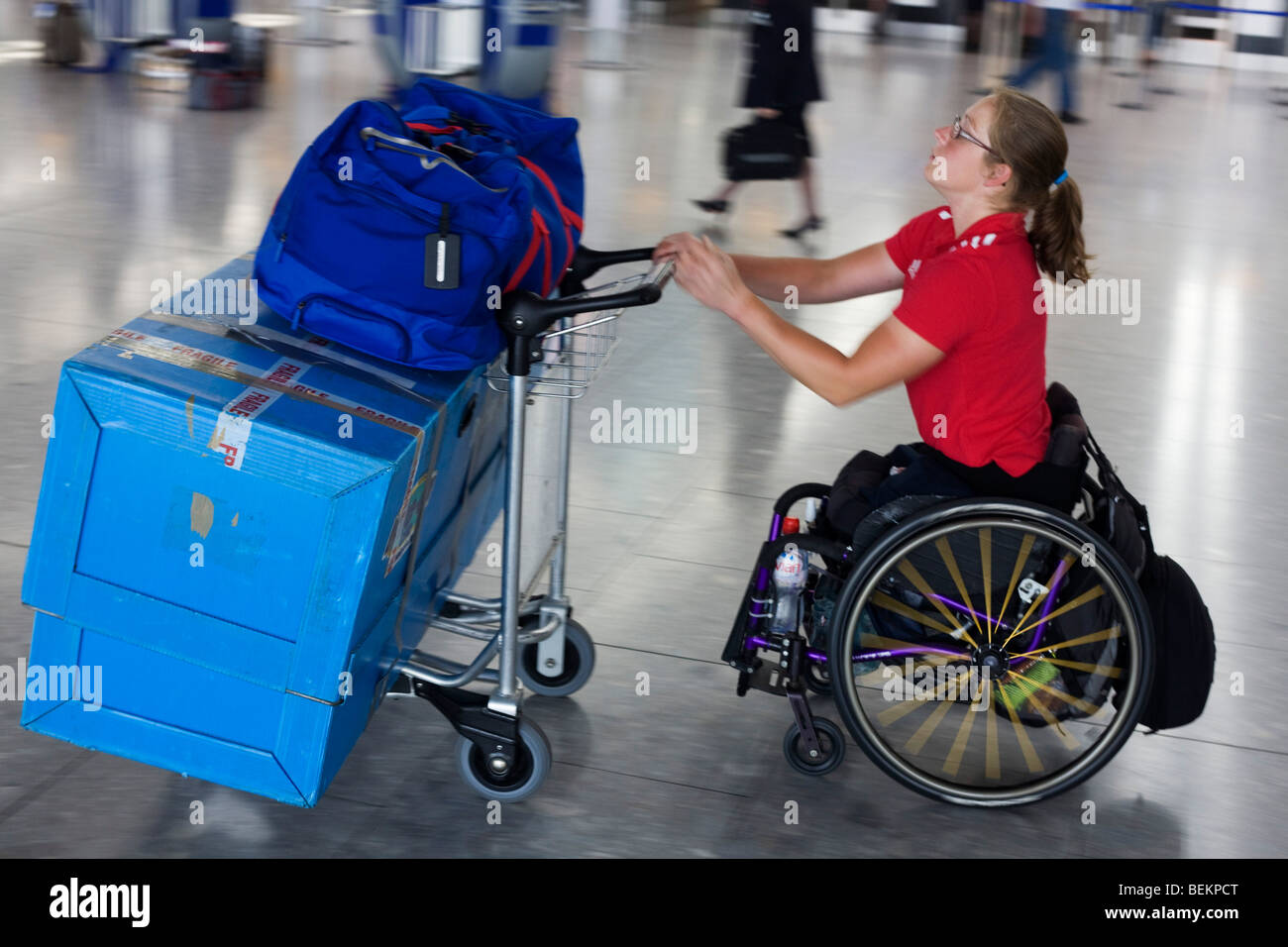 A disabled airline passenger makes her own way through the Departures concourse of Heathrow Airport. - Stock Image