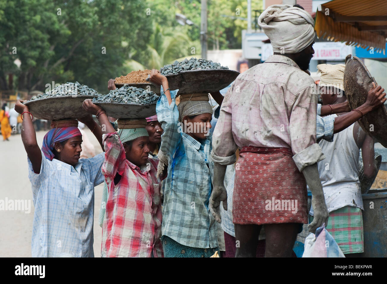 Indian women carrying stones in metal bowls on their heads, to make concrete on an India building site. Andhra Pradesh, - Stock Image