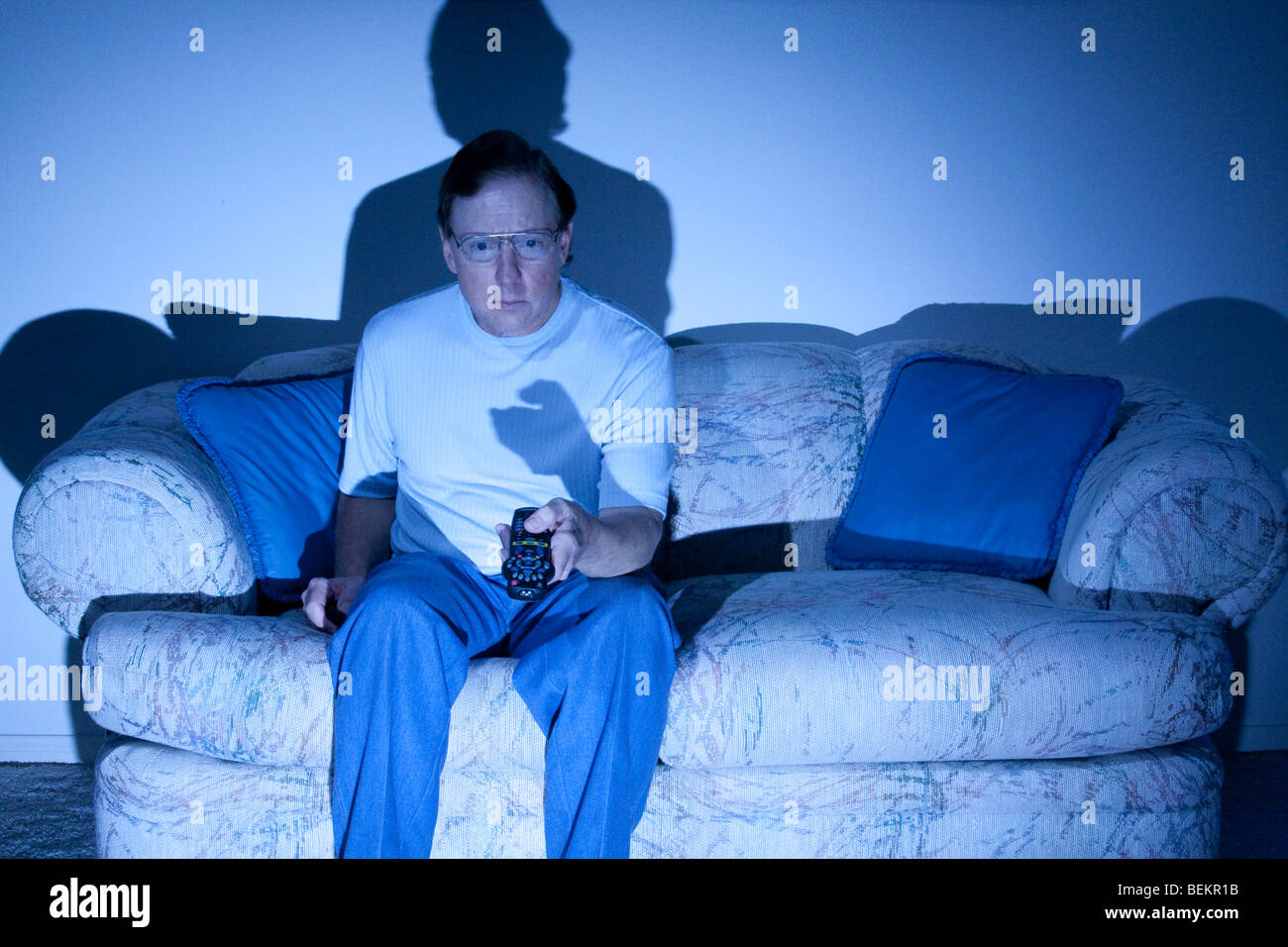 Mature man in shirt and blue jeans wearing glasses sitting on sofa in the dark with tv remote lit by tv screen - Stock Image