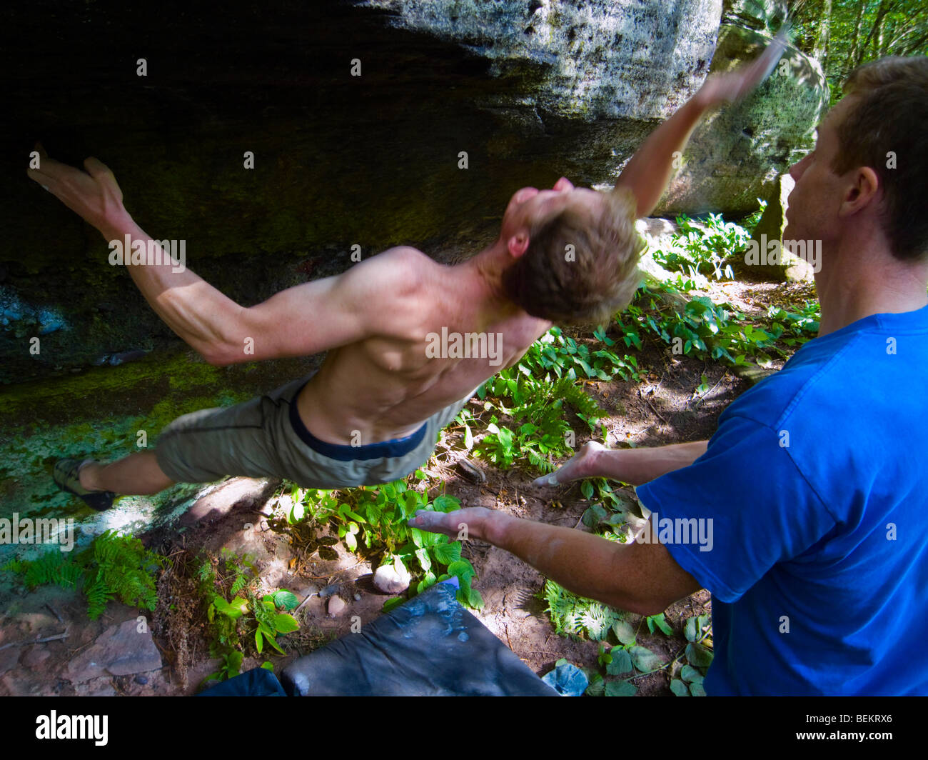 Climber being spotted doing a boulder problem in the Churnet Valley Staffordshire - Stock Image